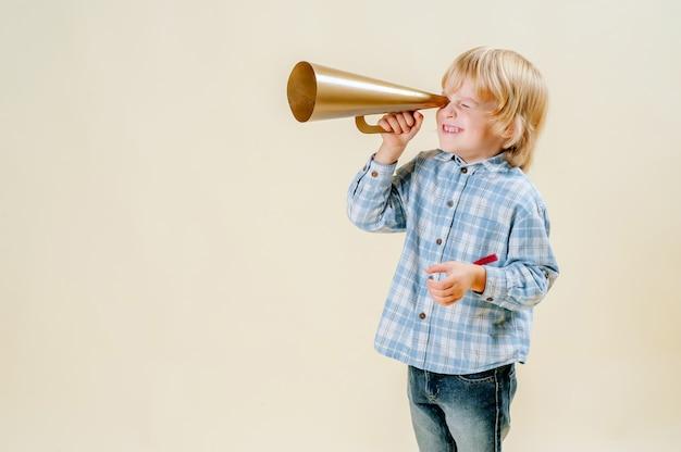 Um pequeno garoto loiro usando telescópio