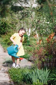 Um pequeno jardineiro ajuda os pais a cuidar do jardim e rega os brotos das plantas da ...