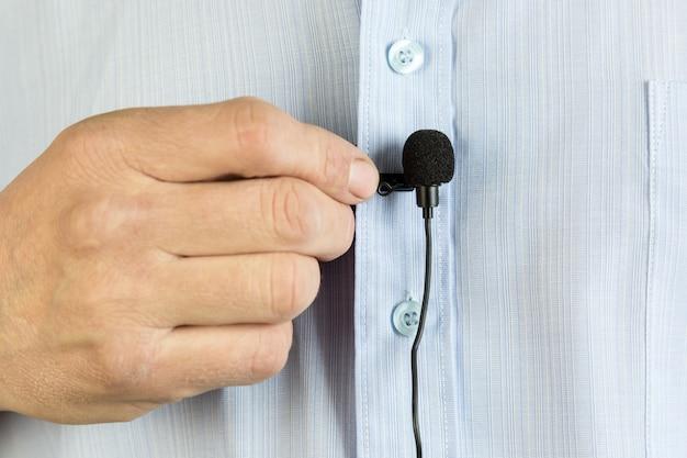 Um pequeno microfone de botão em uma camisa de homem.