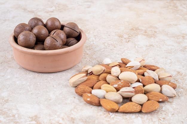 Um pequeno pacote de amêndoas e pistache ao lado de uma tigela de bolas de chocolate