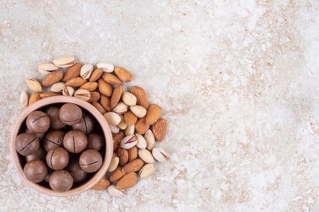 Um pequeno pacote de amêndoas e pistache em torno de uma tigela de bolas de chocolate