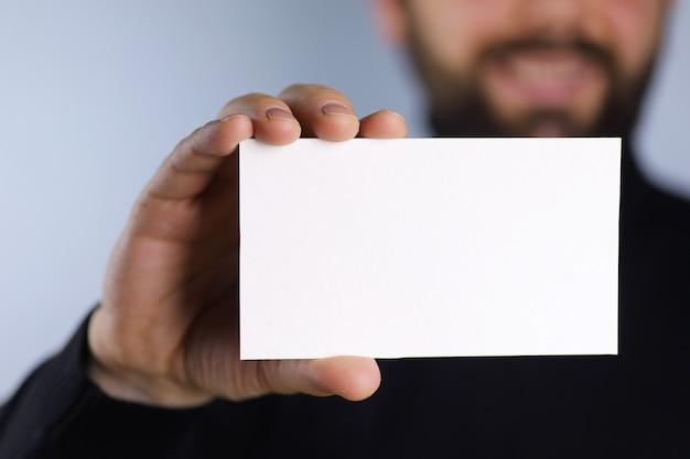 Um pequeno pedaço de papel branco na mão do homem