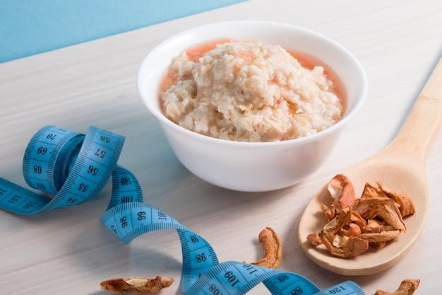 Um pequeno prato branco com aveia fervida, derramada com calda, uma colher grande de madeira com maçãs secas e uma fita métrica azul sobre uma mesa de madeira