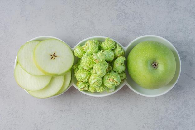 Um pequeno prato de maçãs e superfície de mármore candyon pipoca