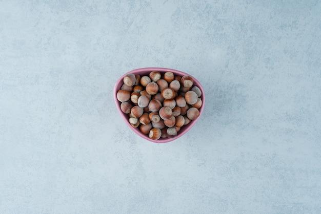 Um pequeno prato rosa cheio de nozes sobre fundo de mármore. foto de alta qualidade