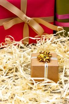 Um pequeno presente embrulhado em papel artesanal e amarrado com uma fita branca parabéns aos entes queridos