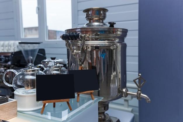 Um pequeno quadro negro com uma área vazia para texto ou mensagem em uma barra de madeira em um café ao lado de bules de vidro e um samovar. quadro negro em um café