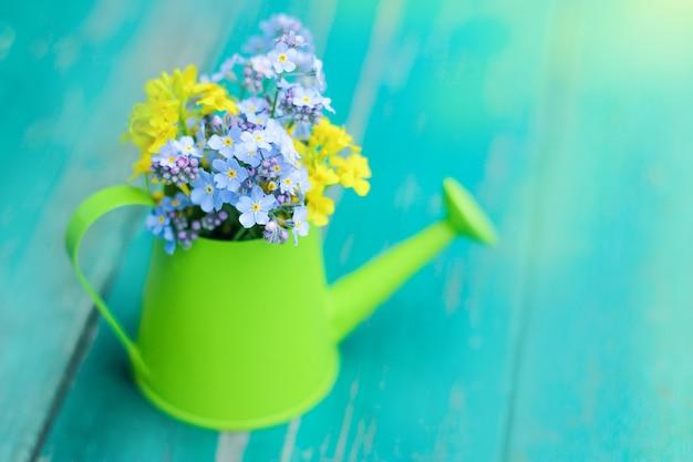 Um pequeno regador verde com um mini buquê de flores silvestres.