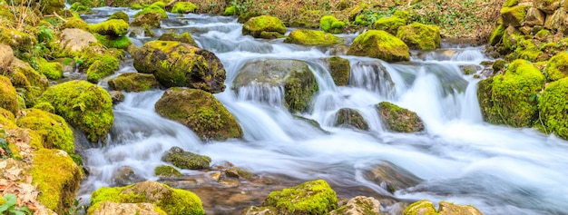 Um pequeno riacho com uma cachoeira e rochas cobertas de musgo na primavera