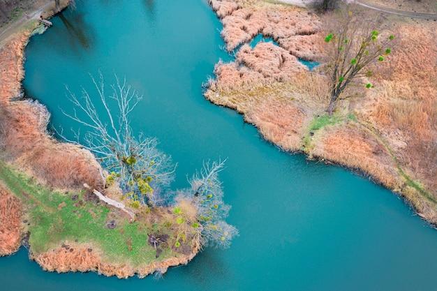 Um pequeno rio com juncos secos nas margens.