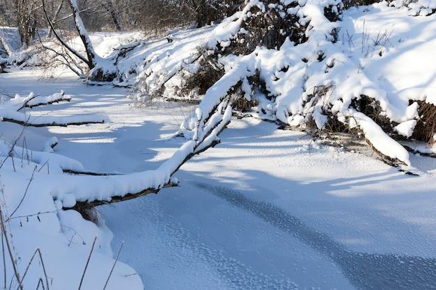 Um pequeno rio cuja água é congelada no inverno, um rio congelado durante as geadas de inverno, neve e geada na natureza no inverno perto de um rio ou lago