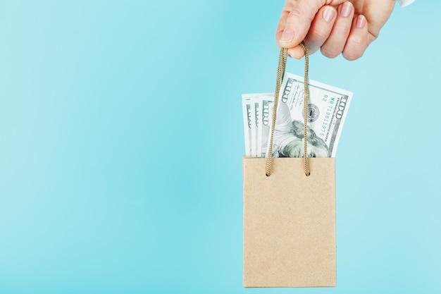 Um pequeno saco de papel para ajuda financeira e suporte de papel no comprimento do braço, com dólares americanos, sobre um fundo azul. o conceito de apoio financeiro insignificante nos negócios,