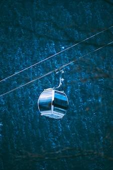 Um pequeno teleférico de esqui se move rapidamente no teleférico do centro da cidade para as pistas de esqui no resort de inverno