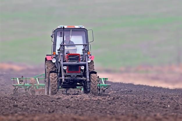 Um pequeno trator com arado ara o campo após a colheita.