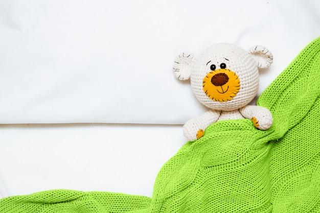 Um pequeno urso de brinquedo de bebê amigurumi de malha é coberto com um cobertor verde