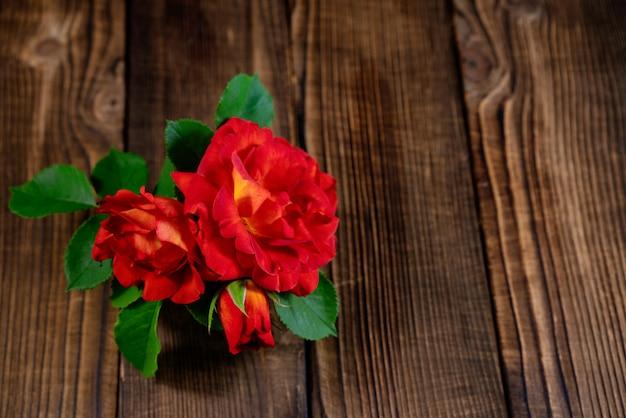 Um pequeno vaso de rosas vermelhas em uma mesa de madeira.