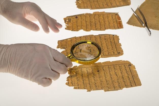 Um pesquisador estuda a escrita árabe do alcorão usando uma lupa e uma mesa com luz