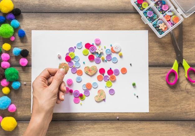 Um, pessoa, decorando, papel branco, com, coloridos, botões, sobre, tabela madeira