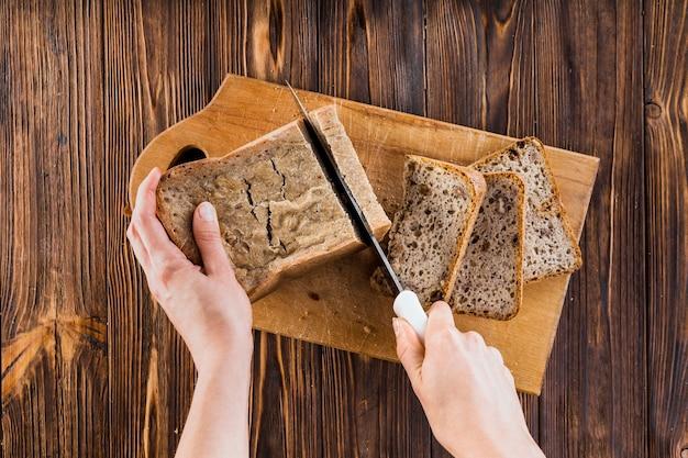 Um, pessoa, fazer, fatias pão, com, faca, ligado, tábua cortante