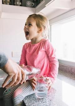 Um, pessoa, mão, despejar, água, em, vidro, enquanto, menina, sentando, ligado, contador cozinha