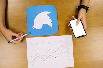 Um, pessoa, segurando, telefone móvel, analisar, a, twitter, gráfico