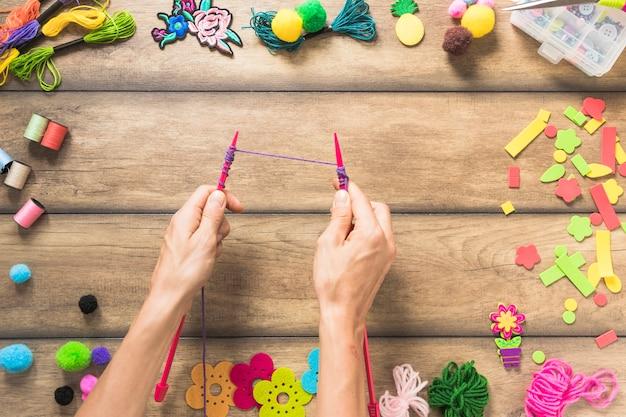 Um, pessoa, tricotando, com, cor-de-rosa, agulhas, ligado, tabela madeira