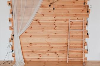 Um photozone de madeira, decorado com lúpulo, com lâmpadas e escada.