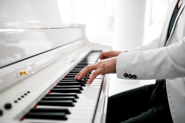 Um pianista de terno branco toca piano