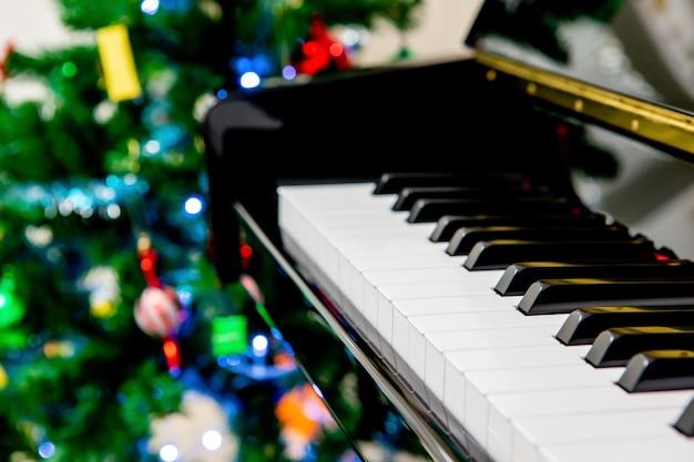 Um piano com fundo de árvore de natal, foco superficial na tecla d.