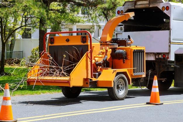 Um picador de árvores ou picador de madeira é uma máquina portátil usada para reduzir a madeira em lascas de madeira menores soprando galhos de árvores cortados na parte de trás de um caminhão. tempestade danifica árvore após uma tempestade
