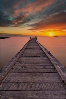Um píer se estendendo para o mar com o pôr do sol