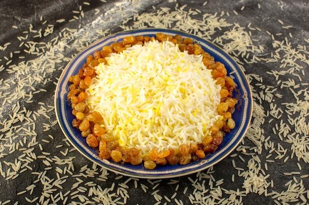 Um pilaf saboroso de vista superior com óleo e passas secas dentro da placa com arroz cru na superfície escura