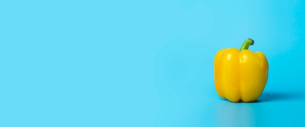 Um pimentão amarelo sobre uma superfície azul. vista superior, configuração plana. bandeira.