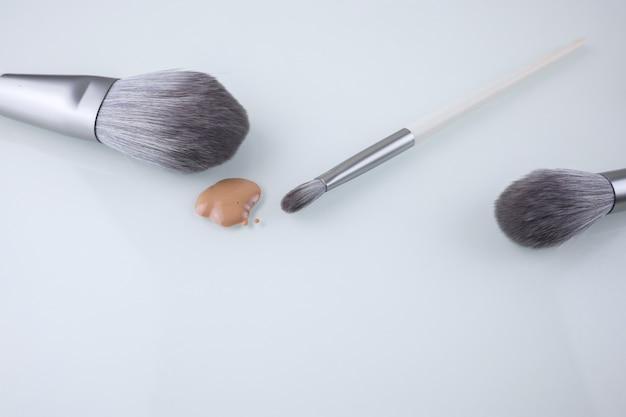 Um pincel de maquiagem e uma gota de base para o rosto