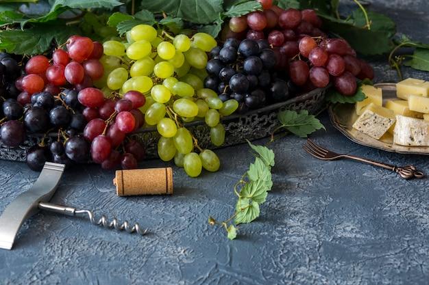 Um pincel de uvas leves, vermelhas e escuras, saca-rolhas, cortiça de vinho e prato de prata com queijo e garfo