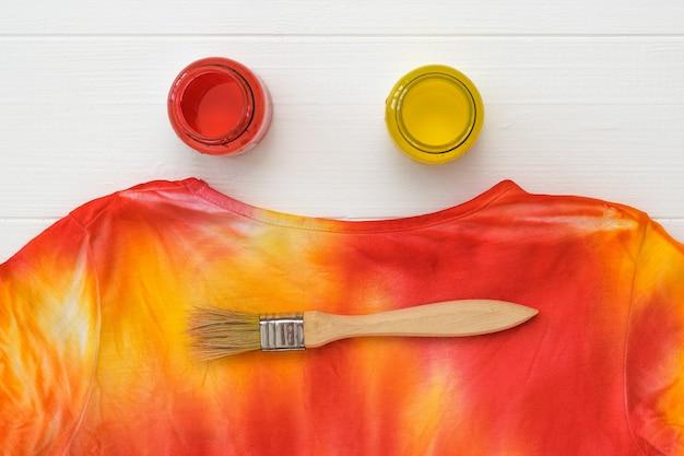 Um pincel, duas latas de tinta e uma camiseta brilhante tie dye em uma mesa branca.