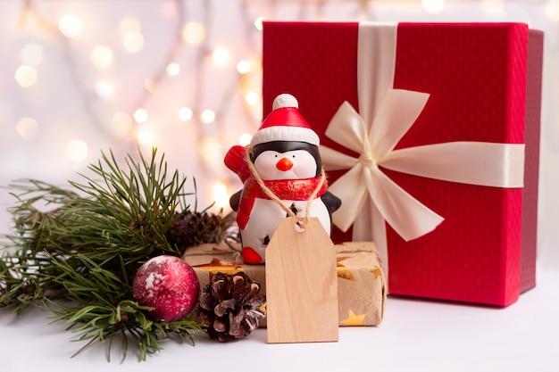 Um pinguim de brinquedo com uma forma em branco de madeira para um texto de saudação perto de uma caixa de presente vermelha. decoração de natal