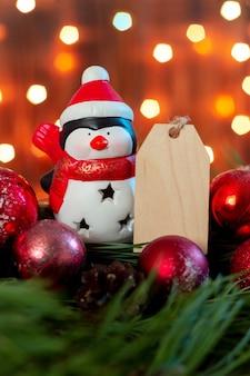 Um pinguim do papai noel de brinquedo com uma forma em branco de madeira para um texto de saudação em um galho de uma árvore de natal
