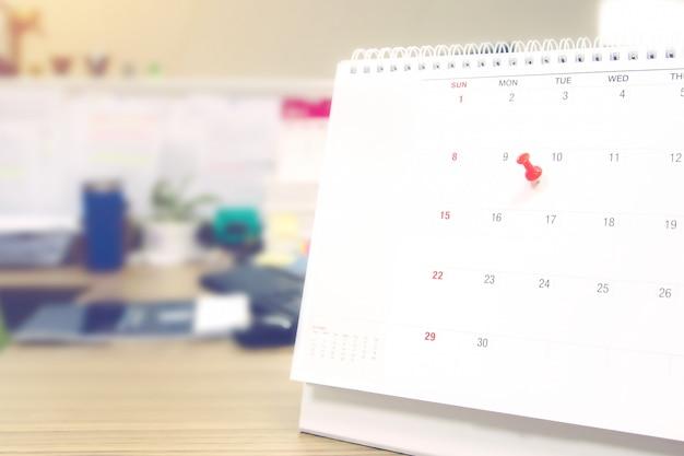 Um pino de cor vermelha no conceito de calendário para planejador de eventos.