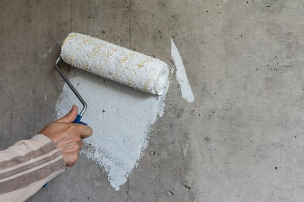Um pintor pinta uma parede de concreto com tinta branca, uma mão masculina com um rolo de pintura para pintar uma parede