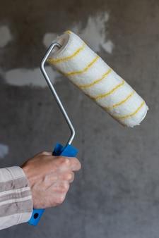 Um pintor pinta uma parede de concreto, uma mão masculina com um rolo de pintura para pintar uma parede