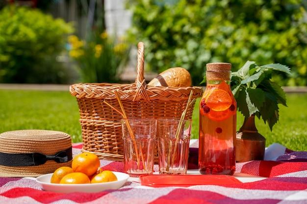 Um piquenique na grama um cobertor xadrez vermelho uma cesta de vime uma bebida natural feita de laranja e berr ...