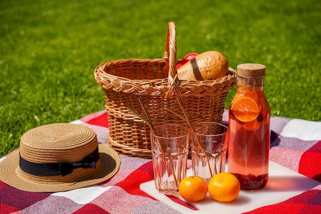 Um piquenique na grama um cobertor xadrez vermelho uma cesta de vime uma bebida natural feita de laranjas e frutas um pão delicioso lanche ao ar livre no verão