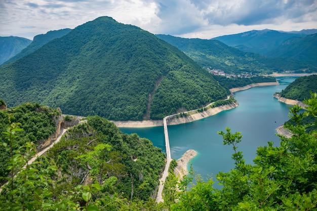 Um pitoresco lago turquesa pode ser visto do topo de uma montanha alta.