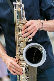 Um plano de closeup de saxofonista de camisa preta