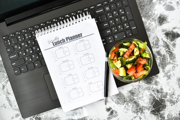 Um plano de refeições para uma semana e uma tigela com salada de legumes no local de trabalho perto do computador