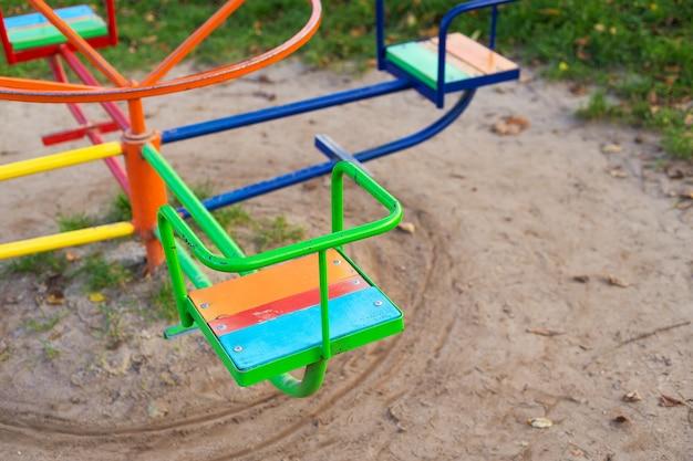 Um playground bem iluminado, diversos balanços infantis, um lindo e aconchegante parque para recreação.