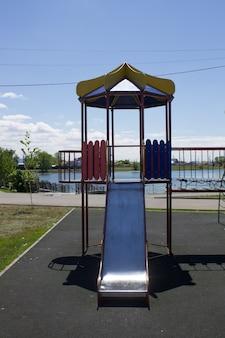 Um playground vazio, multicolorido e seguro com um escorregador no parque da cidade Foto Premium