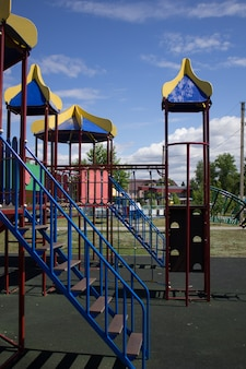 Um playground vazio, multicolorido e seguro com um escorregador no parque da cidade
