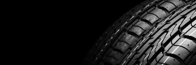 Um pneu de borracha isolante preto, no fundo preto